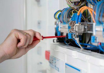 Handwerker Elektriker schraubt im Sicherungskasten.